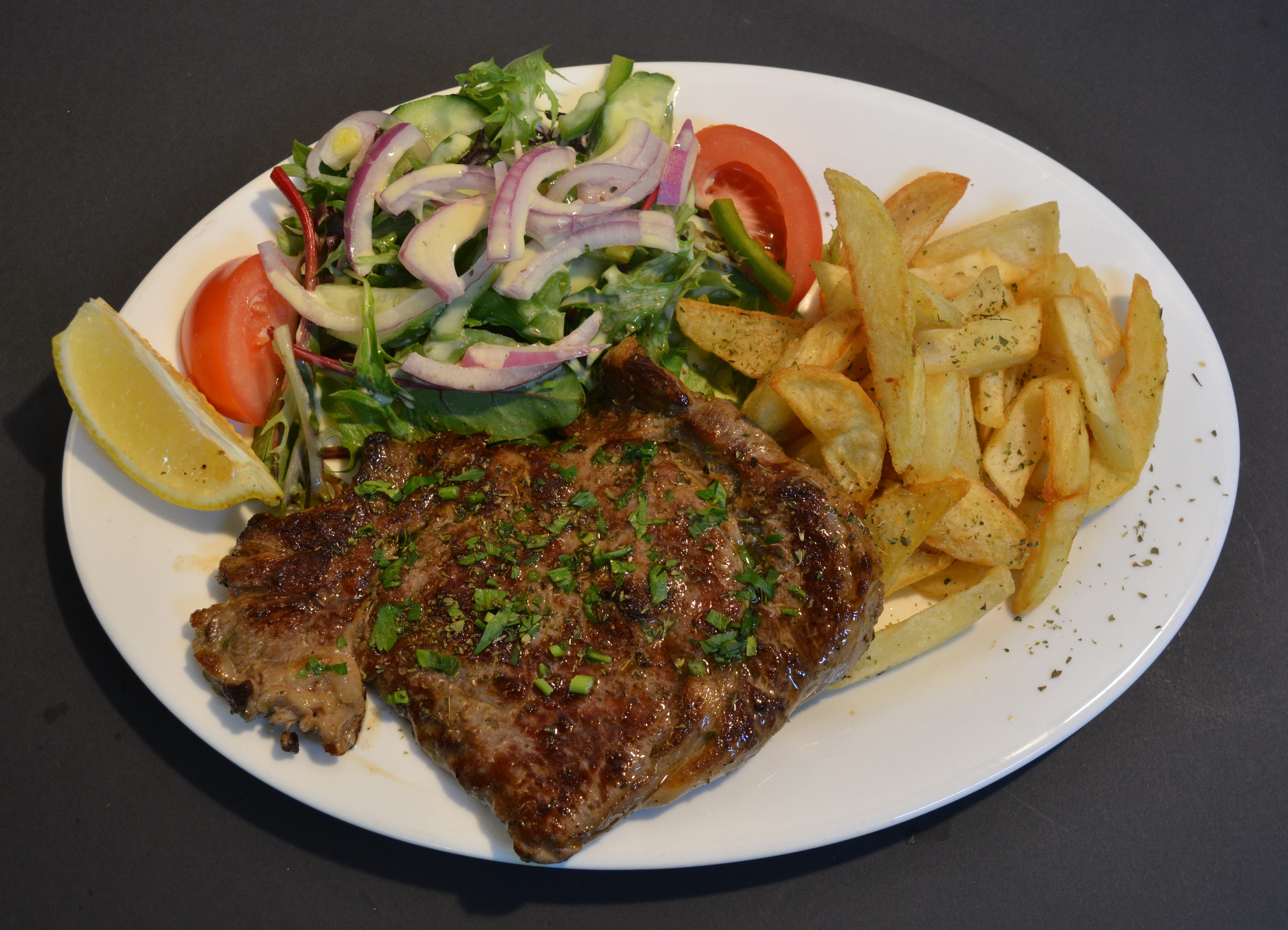 Grilled Beef Cutlets served with homemade chips and salad.