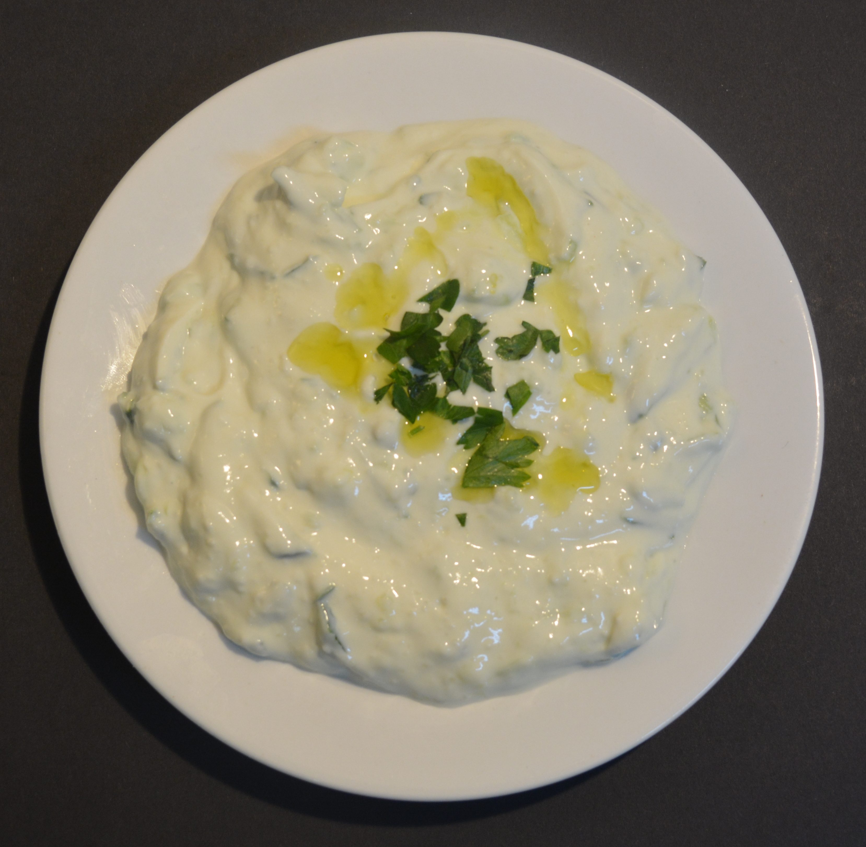 Tzatziki is made of salted strained yogurt or diluted yogurt mixed with cucumbers, garlic, salt, olive oil, sometimes with vinegar or lemon