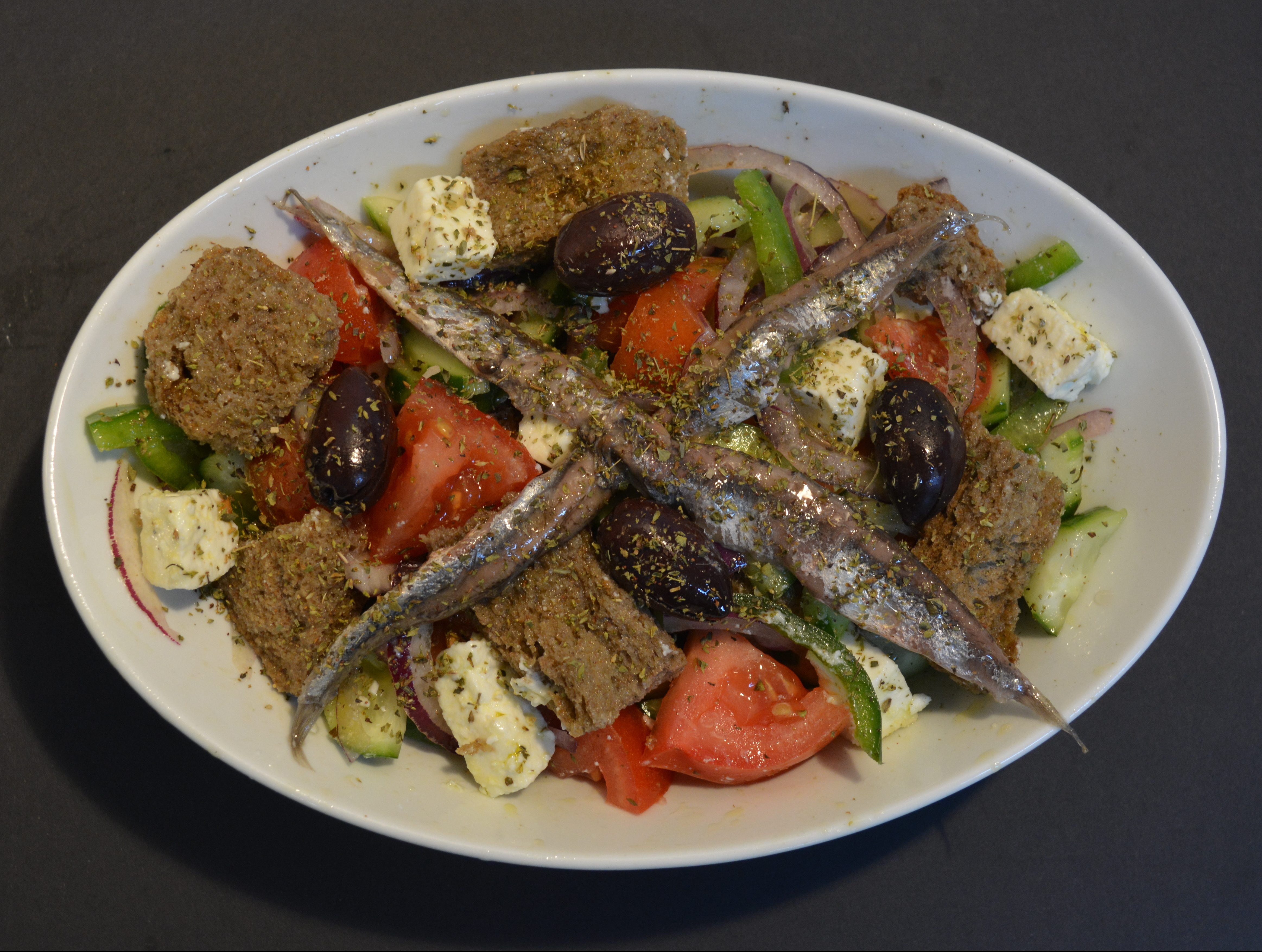 Greek Island Salad, including tomato, cucumber, capsicum, onion, olives, feta cheese, dry bread sticks, anchovies, extra virgin olive oil, oregano.