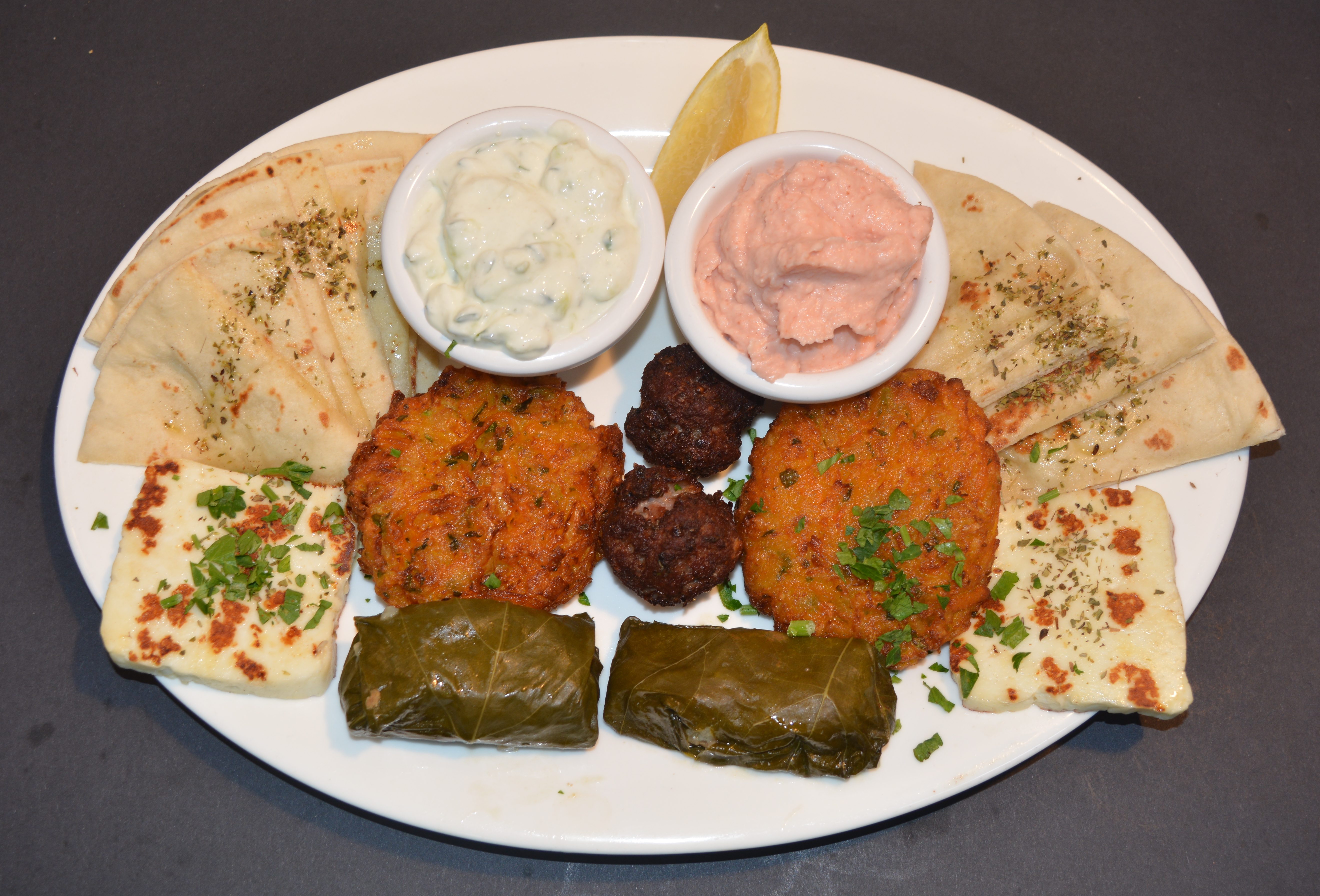 Meze Plate for 2 people, includes taramosalata, tzatziki, pita bread, keftedes (meatballs), fried pumkin patties, dolmades, grilled haloumi cheese.